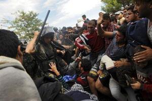 Macedonian police officer raises baton towards Muslim migrants to stop them from entering Macedonia at the Greek border 8-22-2015. (–Reuters/Alexandro Avramidis)